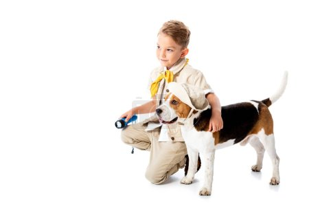 Photo for Smiling explorer child embracing cute beagle dog in hat and holding flashlight on white - Royalty Free Image