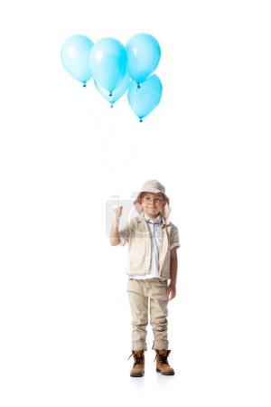 Photo pour Vue pleine longueur de l'enfant explorateur dans des lunettes tenant des ballons bleus isolés sur blanc - image libre de droit