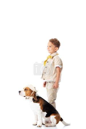 Photo pour Vue pleine longueur de l'enfant d'explorateur de sourire et du crabot mignon de beagle dans le chapeau d'isolement sur le blanc - image libre de droit