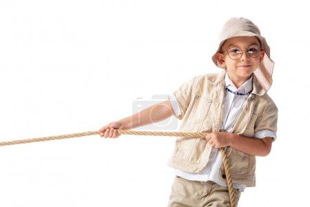 Photo pour Enfant explorateur souriant dans le chapeau et les lunettes tenant la corde et regardant la caméra isolée sur blanc - image libre de droit