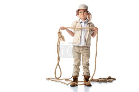 full length view of explorer kid in hat and glasses holding rope on white