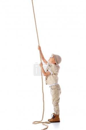 Photo pour Vue pleine longueur du gamin explorateur concentré dans le chapeau et les lunettes tenant la corde isolée sur blanc - image libre de droit