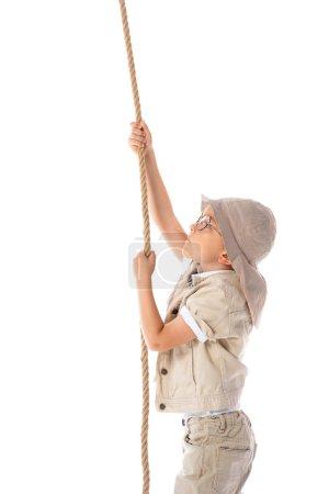 Photo pour Vue latérale du gosse focalisé d'explorateur dans le chapeau et les glaces retenant la corde d'isolement sur le blanc - image libre de droit