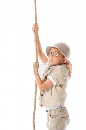 focused explorer kid in hat and glasses holding rope isolated on white