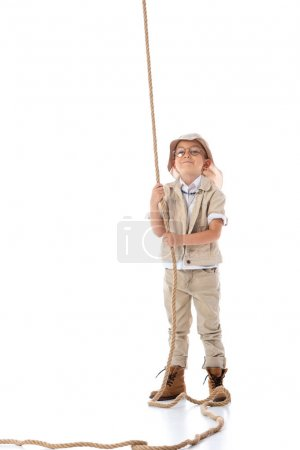 Photo for Full length view of smiling explorer kid in hat and glasses holding rope on white - Royalty Free Image