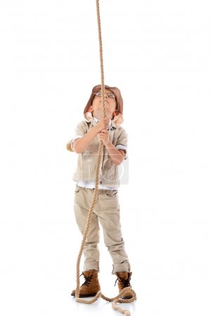 full length view of explorer kid in hat and glasses holding rope and looking up on white
