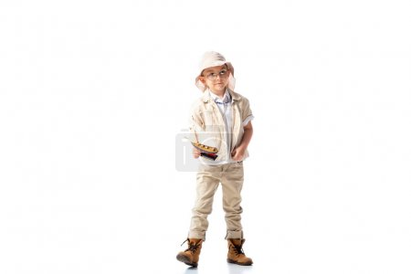 Photo for Full length view of explorer child in glasses and hat holding toy ship on white - Royalty Free Image