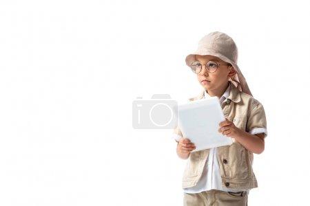Photo pour Enfant explorateur coûteux dans des lunettes et chapeau tenant tablette numérique et regardant loin isolé sur blanc - image libre de droit