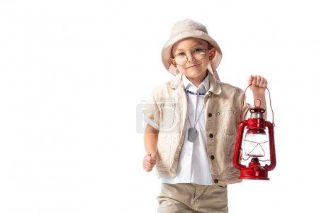 Photo pour Vue de face de garçon explorateur souriant dans des lunettes et chapeau tenant lanterne rouge et regardant la caméra isolée sur blanc - image libre de droit