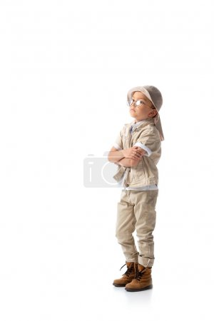 Photo for Full length view of pensive explorer boy in hat and glasses with crossed arms isolated on white - Royalty Free Image