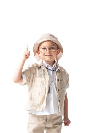 Photo for Front view of smiling explorer boy in glasses and hat looking at camera and showing idea sign isolated on white - Royalty Free Image