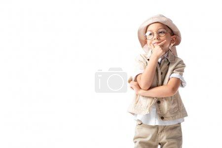Photo pour Cher garçon explorateur dans des lunettes et chapeau toucher le menton et regarder loin isolé sur blanc - image libre de droit