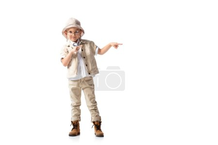 Photo for Full length view of smiling explorer boy in hat and glasses pointing with fingers isolated on white - Royalty Free Image