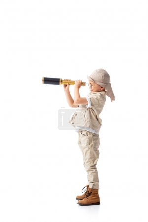 Photo pour Vue pleine longueur de garçon explorateur dans des lunettes et chapeau regardant à travers le verre espion isolé sur blanc - image libre de droit