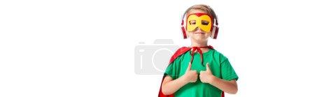 Photo pour Plan panoramique de garçon souriant en costume de héros écoutant de la musique dans les écouteurs et montrant pouces isolés sur blanc - image libre de droit