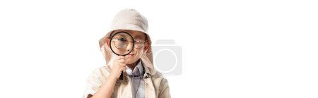panoramic shot of curious explorer boy in hat looking through magnifier isolated on white