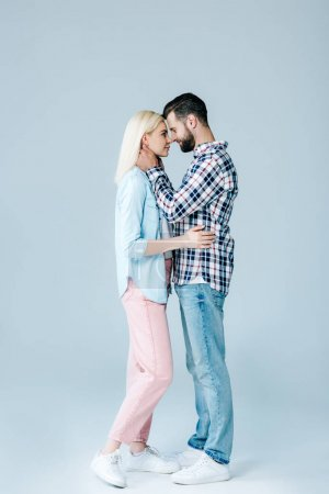Photo for Beautiful young couple hugging and looking at each other on grey - Royalty Free Image