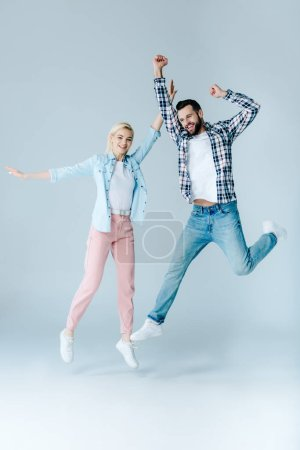 Photo for Happy man and girl in casual clothes jumping on grey - Royalty Free Image