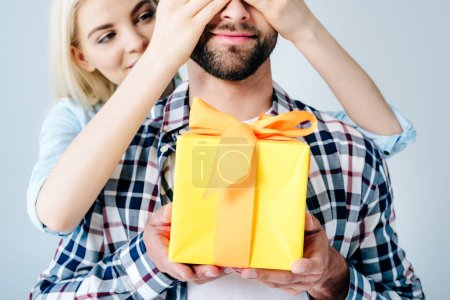 Photo for Beautiful girl Covering Eyes of man holding present isolated on grey - Royalty Free Image