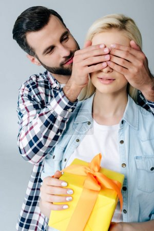 Photo for Man Covering Eyes of young woman with gift isolated on grey - Royalty Free Image