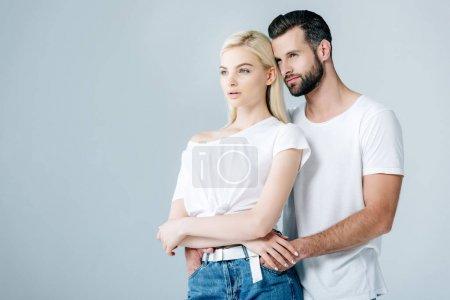 Foto de Hermosa pareja joven abrazando y mirando hacia otro lado aislado en gris - Imagen libre de derechos