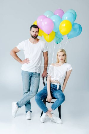 Photo for Man and beautiful girl on chair near balloons on grey - Royalty Free Image