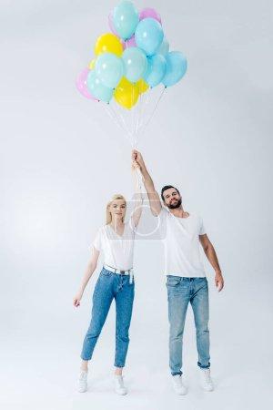 Foto de Hombre y hermosa chica sosteniendo globos en gris - Imagen libre de derechos