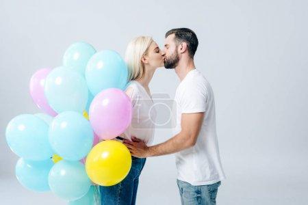 Photo pour Homme et belle fille avec des ballons embrasser isolé sur gris - image libre de droit