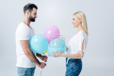 Photo for Man and beautiful girl holding balloons on grey - Royalty Free Image