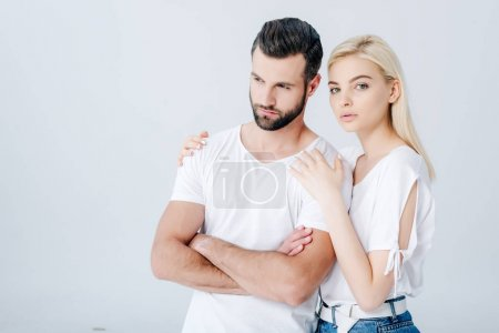 Photo for Beautiful young woman embracing upset man with crossed arms isolated on grey - Royalty Free Image