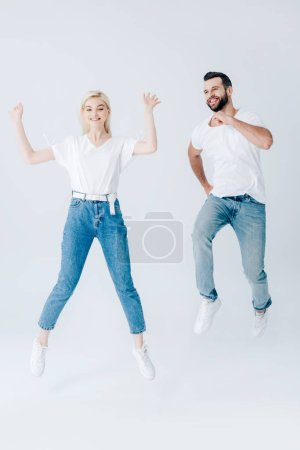Photo for Excited man and young woman jumping and gesturing on grey - Royalty Free Image