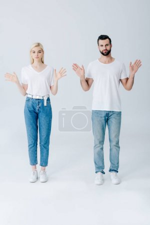 Photo for Man and young woman posing with open palms isolated on grey - Royalty Free Image