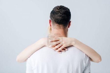Photo pour Vue arrière de fille embrassant l'homme isolé sur gris - image libre de droit