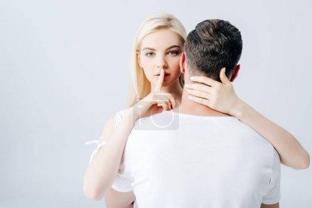 Photo pour Belle fille embrassant l'homme et faisant le geste de silence d'isolement sur le gris - image libre de droit