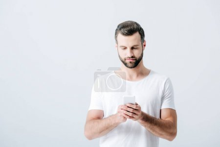 Photo for Good-looking man using smartphone isolated on grey - Royalty Free Image