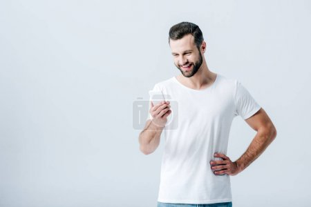 Photo for Smiling handsome man using smartphone isolated on grey - Royalty Free Image