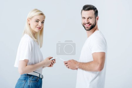 Photo for Smiling man and beautiful girl using smartphones isolated on grey - Royalty Free Image