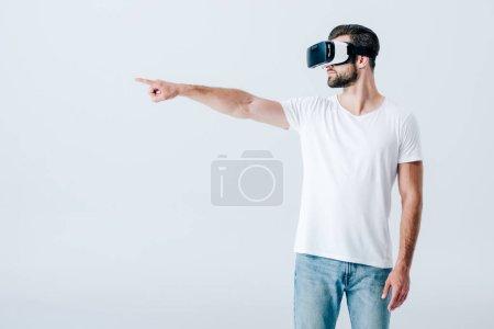 Photo pour Homme barbu dans le casque de réalité virtuelle pointant avec le doigt isolé sur le gris - image libre de droit