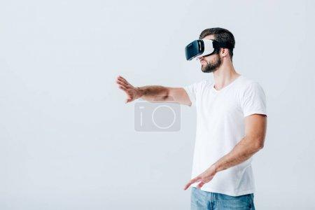 Photo pour Homme barbu dans le casque de réalité virtuelle gesticulant isolé sur le gris - image libre de droit