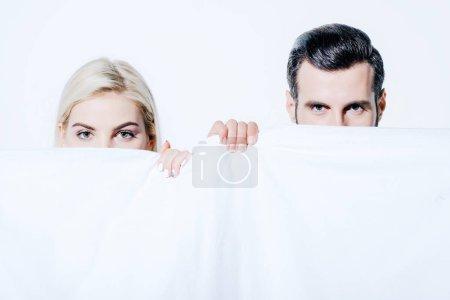 Photo pour Petite amie et petit ami retenant la couverture et regardant l'appareil-photo isolé sur le blanc - image libre de droit