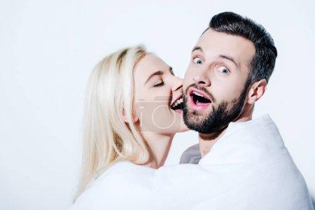 Photo pour Petite amie mordant la joue du petit ami étonné couvert dans la couverture sur le blanc - image libre de droit
