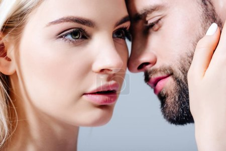 Photo for Beautiful blonde young woman embracing man isolated on grey - Royalty Free Image