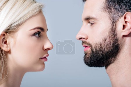 Photo for Handsome man and young woman looking at each other isolated on grey - Royalty Free Image