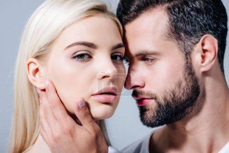 Photo pour Bel homme embrassant doucement belle fille regardant la caméra isolée sur gris - image libre de droit