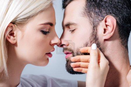 Photo pour Belle fille touchant le visage de l'homme beau d'isolement sur le gris - image libre de droit