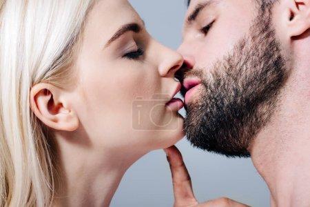 Photo pour Beau couple séduisant embrasser isolé sur gris - image libre de droit