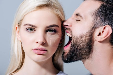 Photo for Man yelling at beautiful young woman looking at camera isolated on grey - Royalty Free Image
