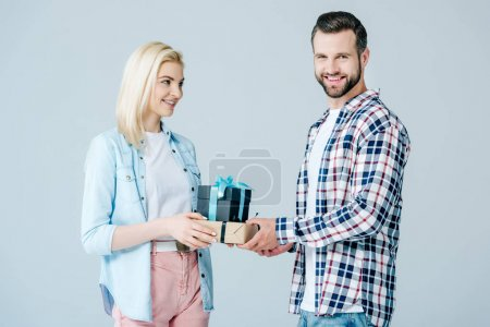 smiling man giving presents to beautiful girl isolated on grey