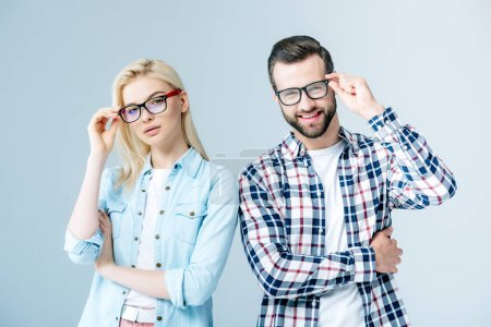 Photo for Man and girl adjusting glasses and looking at camera on grey - Royalty Free Image
