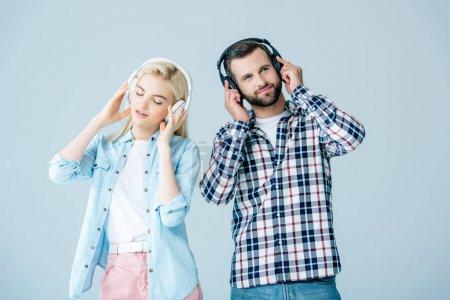 Photo pour Homme et fille dans casque écouter de la musique isolé sur gris - image libre de droit